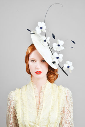 white cinamay with navy quill adorned with white and navy flowers and coque feathers