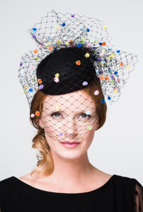 black felt pillbox with black merry widow veiling covered in multi coloured polka dots