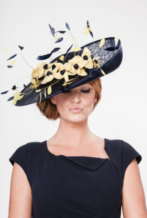 Large navy sinamay hat with yellow hand sewn flowers and navy coque feathers