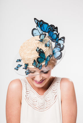 classic straw boater with an opaque brim adorned with a cornucopia of hand cut turquoise butterflies